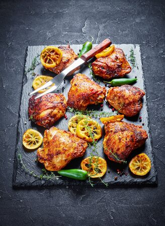 close-up of crispy fried Chicken Thighs With Roasted Lemon Slices, jalapeno peppers and thyme on a black stone tray on a concrete table, view from above
