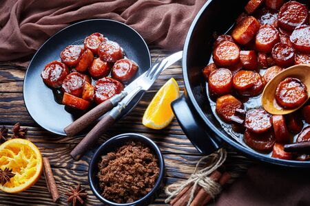 candied yams, sweet potatoes cooked with cinnamon, orange juice, brown sugar and butter in a black ceramic dish. a portion served on a black plate on a rustic wooden table,  horizontal view from above 写真素材