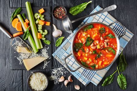 cranberry beans Soup with spinach parmesan and tomato in a metal saucepan on a black wooden table, ingredients on a black stone board, italian cuisine, horizontal view from above, flat lay