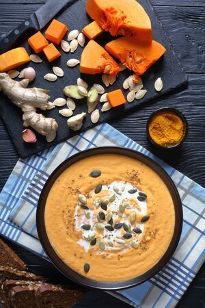 close-up of Creamy Roasted butternut Pumpkin curry sprinkled with pumpkin seeds in a black bowl on a wooden table, ingredients on a slate board, view from above, flatlay