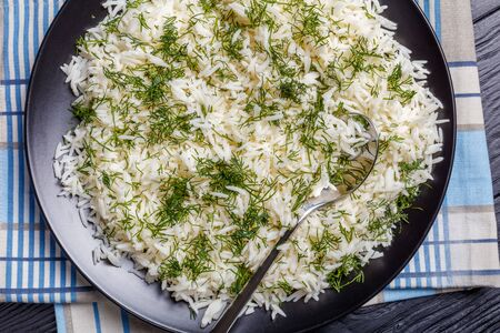 close-up of Shivid Polow, Persian Dill Rice , traditional Persian side dish served on a black platter on a wooden table, view from above, flatlay Banco de Imagens
