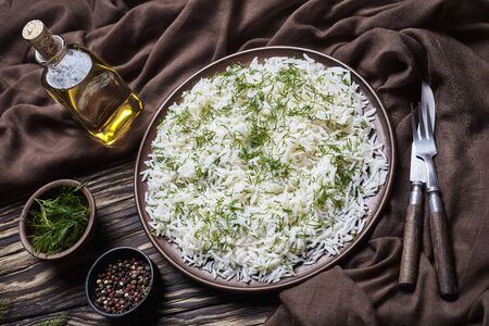 rustic style of classic Shivid Polow, Persian Dill Rice, traditional Persian side dish served on a brown plate on a wooden table, horizontal view from above, close-up Banco de Imagens