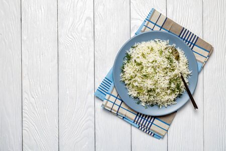 Shivid Polow, Persian Dill Rice, traditional Persian side dish served on a  plate on a white wooden table, horizontal view from above, flatlay, copy space