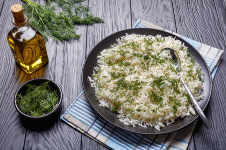 Shivid Polow, Persian Dill Rice, traditional Persian side dish served on a black platter on a wooden table, view from above, close-up