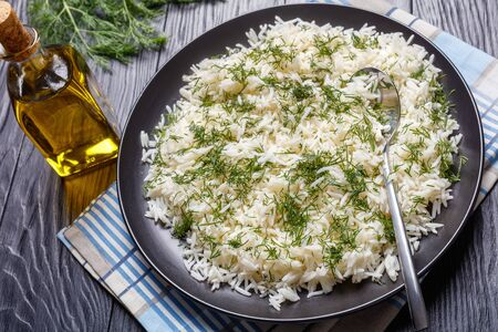 close-up of classic Shivid Polow, Persian Dill Rice , traditional Persian side dish served on a black platter on a wooden table, view from above Banco de Imagens