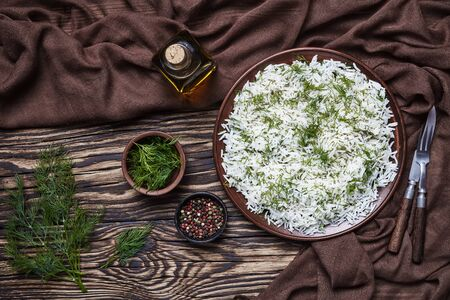 rustic style of classic Sheveed Polo, Persian Dill Rice, traditional Persian side dish served on a brown plate on a wooden table, horizontal view from above, flatlay