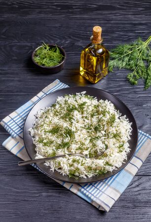 classic Shivid Polow, Persian Dill Rice, traditional Persian side dish served on a black platter on a wooden table, vertical view