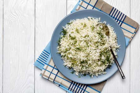 classic Sheveed Polow, Persian Dill Rice, traditional Persian side dish served on a  plate on a white wooden table, horizontal view from above, flatlay, free space