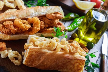 close-up of sandwiches with calamari rings, Bocadillos De Calamares, fresh bread roll filled with squid rings that have been coated in flour and in breadcrumbs and deep-fried in olive oil