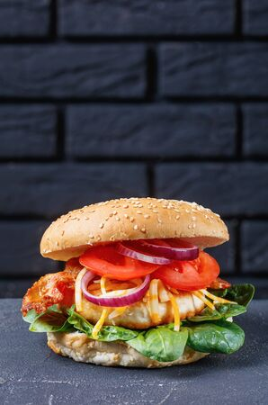 vertical view of homemade turkey burgers on buns with shredded marble cheese, crispy fried bacon, tomato slices, spinach leaves, and red onion on a concrete table with a brick wall at the background Stock Photo