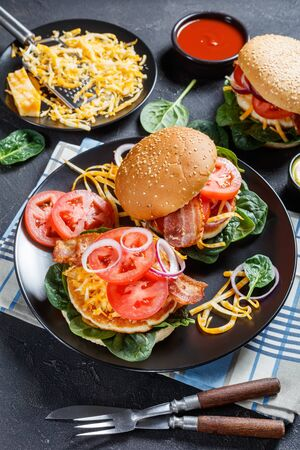 chicken burgers on buns with shredded marble cheese, crispy fried bacon, tomato slices, spinach leaves, and red onion on a black plate, close-up, vertical view Zdjęcie Seryjne