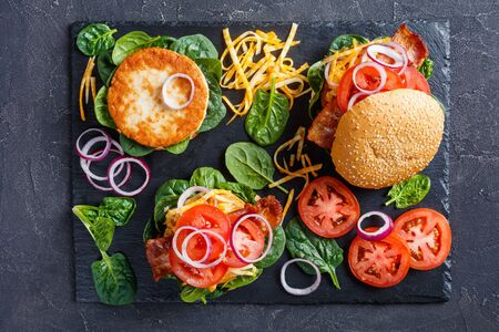 Homemade turkey burgers on buns with shredded marble cheese, crispy fried bacon, tomato slices, spinach leaves, and red onion on a black slate plate, view from above, flat lay Zdjęcie Seryjne