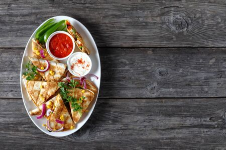 rustic style of grilled mexican chicken quesadillas with vegetables, corn kernels, shredded cheddar cheese, olives and mushrooms on a white oval platter with tomato salsa, view from above, flat lay