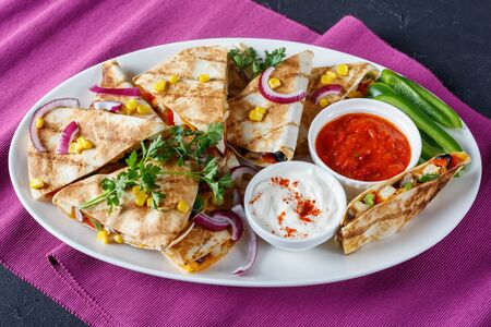 mexican chicken quesadilla with vegetables, corn kernels, shredded cheddar cheese, olives and mushrooms on a white oval platter with tomato salsa and sour cream, view from above Reklamní fotografie - 133696524