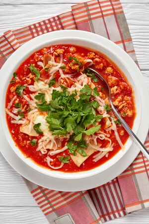 close-up of chicken lasagna soup in a white bowl on a wooden table, american italian cuisine, vertical  view from above Foto de archivo