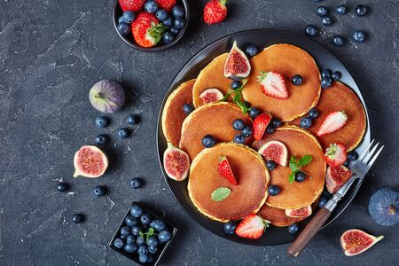 almond flour pancakes on a black plate with strawberries, blueberries, figs and mint, on a concrete table, vertical view from above, macro, flat lay