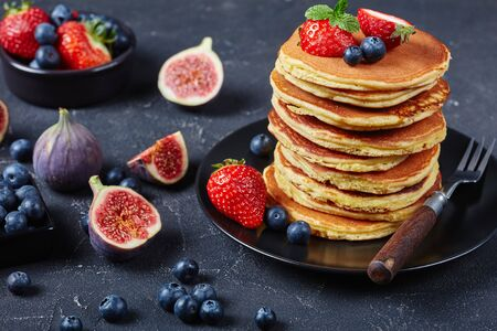 stack of almond flour healthy pancakes on a black plate with figs, strawberries, blueberries and mint, horizontal view from above. close-up