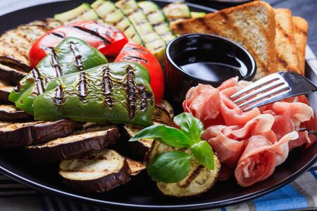 close-up of grilled vegetables, grilled sweet pepper, zucchini slices, eggplants, toasts served on a black plate with thinly sliced ham and vinegar sauce, horizontal view Standard-Bild - 133908875