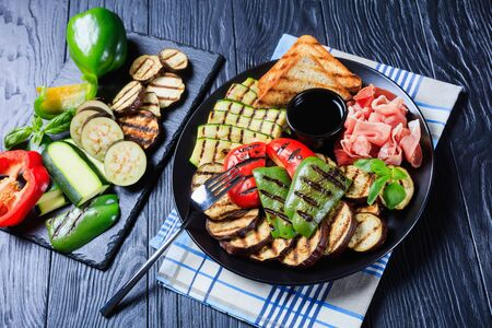 thinly sliced prosciutto ham served with grilled sweet pepper, zucchini slices, eggplants, toasts on a black plate with vinegar sauce. ingredients on a slate tray 스톡 콘텐츠