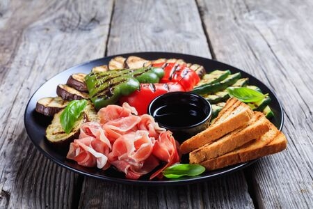 close-up of grilled vegetables, grilled sweet pepper, zucchini slices, eggplants, toasts served on a black plate with thinly sliced ham and vinegar sauce