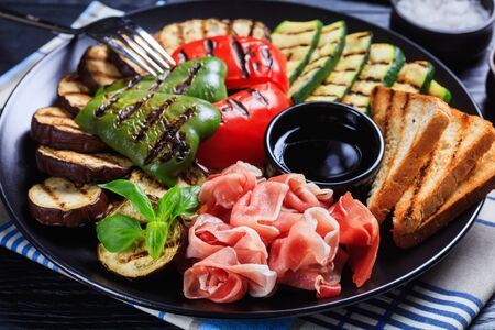 close-up of thinly sliced prosciutto ham served with grilled sweet pepper, zucchini slices, eggplants, toasts on a black plate with vinegar sauce 스톡 콘텐츠