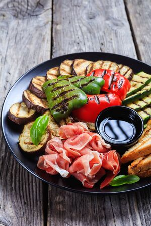 close-up of grilled vegetables, grilled sweet pepper, zucchini slices, eggplants, toasts served on a black plate with thinly sliced ham and vinegar sauce,  vertical view