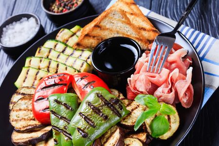 close-up of grilled vegetables, grilled sweet pepper, zucchini slices, eggplants, toasts served on a black plate with thinly sliced ham and vinegar sauce, horizontal view  스톡 콘텐츠