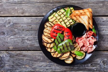 overhead view of thinly sliced prosciutto ham served with grilled sweet pepper, zucchini slices, eggplants, toasts on a black plate on a rustic wooden table, flatlay, copy space 스톡 콘텐츠