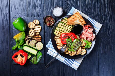 thinly sliced prosciutto ham served with grilled sweet pepper, zucchini slices, eggplants, toasts on a black plate with vinegar sauce. ingredients on a slate tray, flatlay 스톡 콘텐츠
