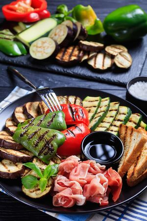 close-up of grilled vegetables, grilled sweet pepper, zucchini slices, eggplants, toasts served on a black plate with thinly sliced ham and vinegar sauce, ingredients at the background, vertical view