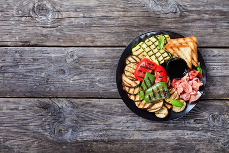 thinly sliced prosciutto ham served with grilled sweet pepper, zucchini slices, eggplants, toasts on a black plate on a rustic wooden table, flatlay, copy space Standard-Bild - 133908889