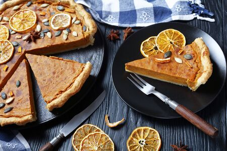 sliced Sweet potato pie decorated with orange chips, pumpkin seeds and anise stars on a black plate on a wooden table, horizontal view