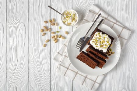 Dark Molasses Gingerbread Cake with fresh whipped cream on top and finely chopped pistachios served on a white plate on a wooden table, horizontal view from above, flatlay, free space