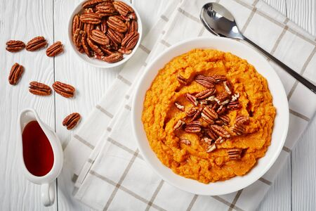 close-up of delicious mashed sweet potato topped with pecan nuts in a bowl. maple syrup in a white sauceboat on a wooden table, horizontal view from above