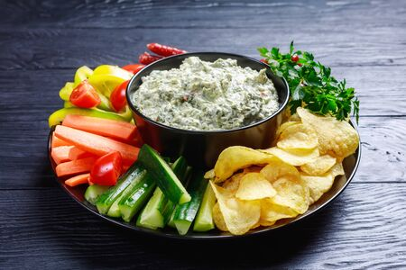 close-up of Creamy spinach dip in a bowl with sausages, carrots, cucumber, sweet pepper sticks, potato chips and fresh parsley on a plate Zdjęcie Seryjne