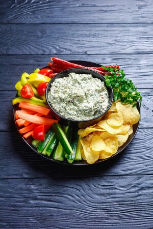 close-up of Creamy spinach dip in a bowl with sausages, carrots, cucumber, sweet pepper sticks, potato chips and fresh parsley on a plate, vertical view from above
