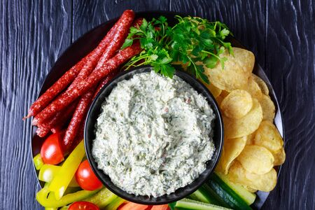 Creamy spinach dip in a bowl with sausages, carrots, cucumber, sweet pepper sticks, potato chips and fresh parsley, view from above, flatlay, close-up, macro Zdjęcie Seryjne