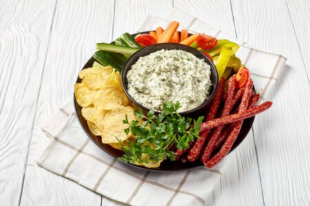 close-up of Creamy spinach dip in a bowl with sausages, carrots, cucumber, sweet pepper sticks, potato chips and fresh parsley on a plate on a white table,  view from above,