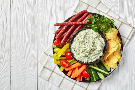 Creamy spinach dip in a bowl with sausages, carrots, cucumber, sweet pepper sticks, potato chips and fresh parsley on a plate on a white table,  view from above, flatlay