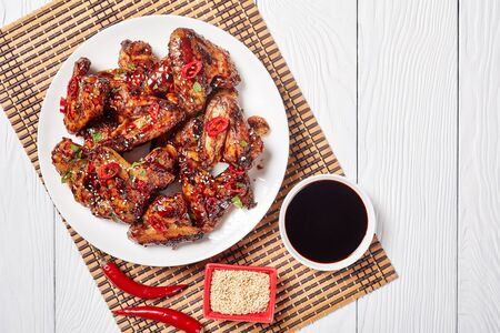 close-up of crispy Teriyaki Chicken Wings sprinkled with sesame seeds, chili pepper pieces and parsley on a white plate on a bamboo mat, view from above, flatlay, free space