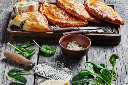 close-up of freshly baked Calzones, closed pizzas with Spinach and Cheese filling sprinkled with grated parmesan on a rude wooden board on a rustic wooden table, italian cuisine