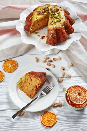 delicious moist pumpkin carrot sponge cake with orange glaze, sprinkled with pistachios on ceramic stand and a slice on a plate on a white wooden table, vertical view