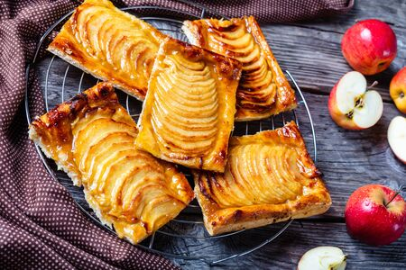 close-up of Caramel Apple puff pastry tarts on a metal stand on a wooden rustic table with brown cloth, horizontal view from above