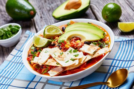 close-up of mexican shredded Chicken Taco Soup with black bean, corn kernels, topped with tortilla strips, avocado slices and lime in white bowl on a rustic wooden table, horizontal view