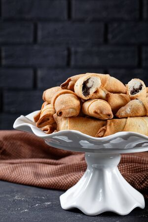 freshly baked mini croissants with poppy seeds and raisins filling on a white cake stand on a concrete table with a brick wall at the background, close-up, vertical view from above