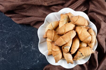 freshly baked mini croissants with poppy seeds and raisins filling on a white plate on a concrete table, flat lay, close-up, horizontal view from above