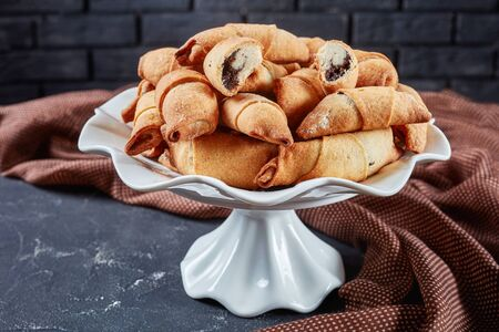 freshly baked mini croissants with poppy seeds and raisins filling on a white cake stand on a concrete table with a brick wall at the background, close-up, horizontal view from above