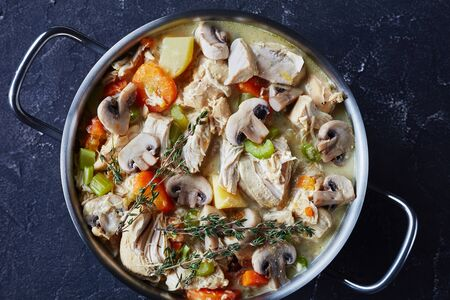 traditional slow cooked chicken stew with vegetables and creamy sauce in a pot on a concrete table, horizontal view from above, flat lay, close-up Zdjęcie Seryjne