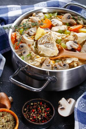 traditional slow-cooked chicken stew with vegetables, mushrooms, herbs and creamy sauce in a pot with a wooden spoon on a concrete table with ingredients, vertical view from above