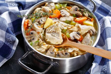 close-up of slow cooked chicken stew with vegetables, mushrooms, herbs and creamy sauce in a pot with a wooden spoon on a concrete table, horizontal view from above